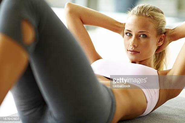 Pretty young lady doing abs exercise