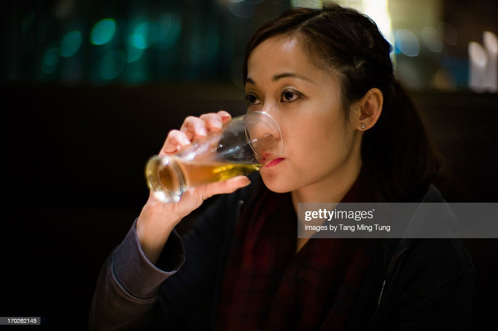 Pretty young lady drinking a glass of beer : Stock Photo