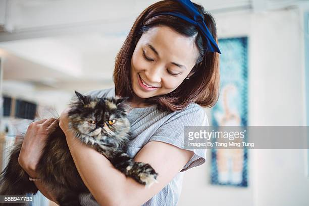 Pretty young lady holding a fluffy cat joyfully