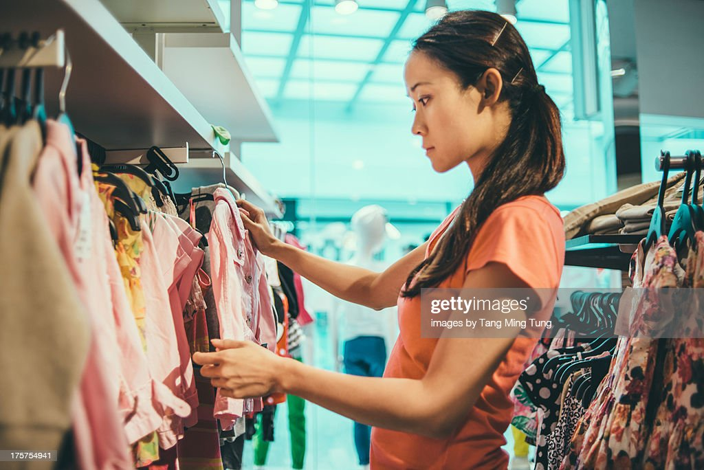 Pretty young lady shopping for toddler clothing : Stock Photo