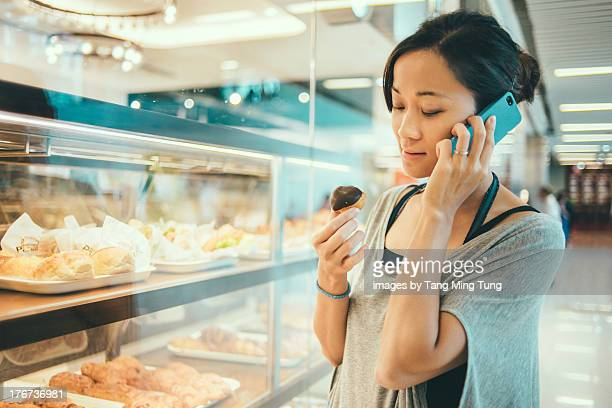 Pretty young lady talking on smartphone in bakery
