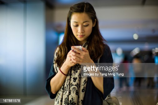 Pretty young lady using smartphone in a mall