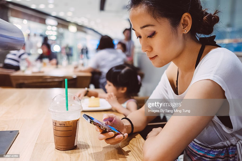 Pretty young lady using smartphone in cafe