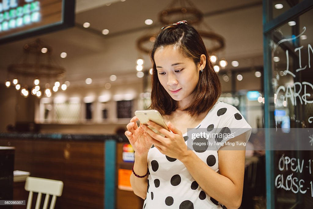 Pretty young lady using smartphone in restaurant