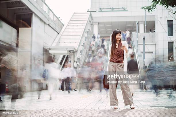 Pretty young lady using smartphone on busy street