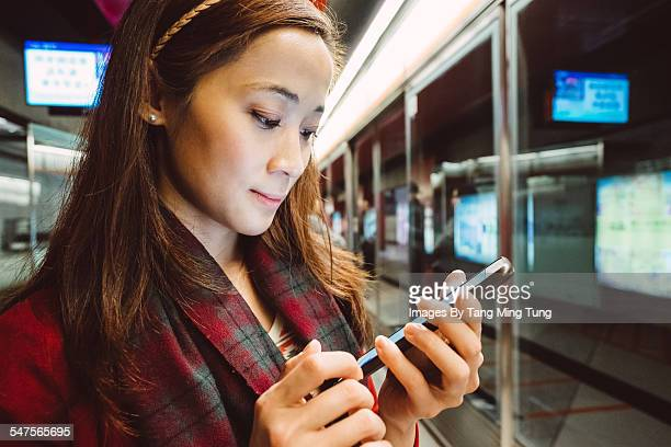 Pretty young lady using smartphone on platform
