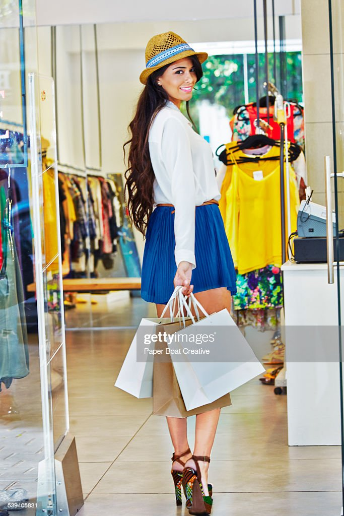 Pretty young lady walking in to a clothes shop