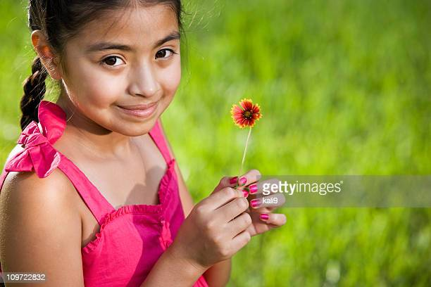 Pretty young Latin girl in pink dress holding flower