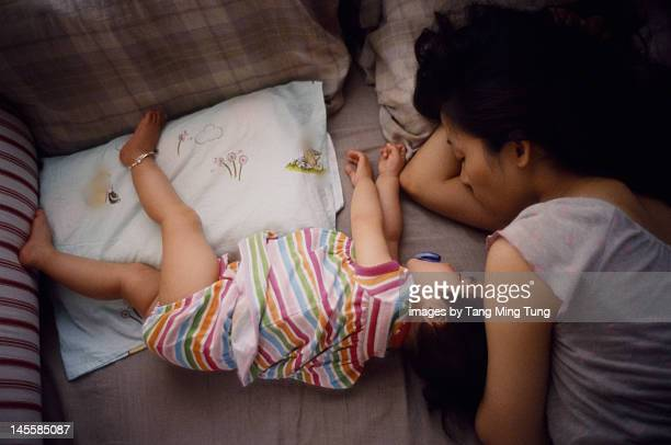Pretty young mom and baby sleep soundly on bed