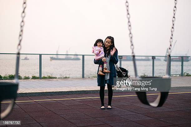 Pretty young mom & baby waving goodbye to swings