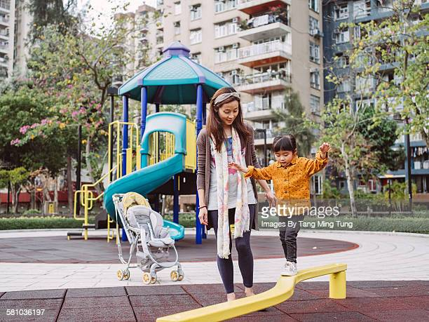Pretty young mom & daughter playing in playground