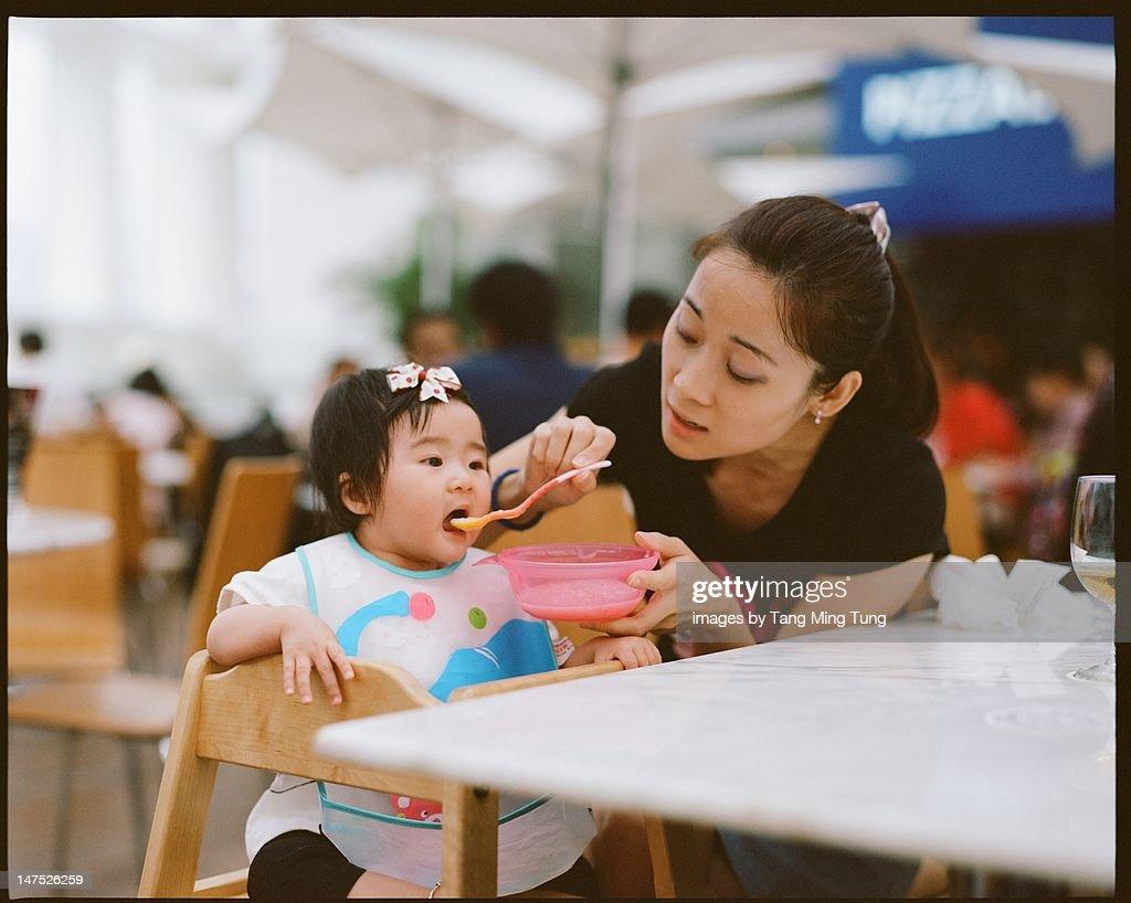 Pretty young mom feeding baby : Stock Photo