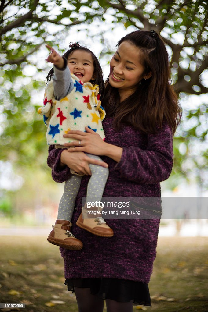 Pretty young mom holding laughing baby joyfully : Stock Photo