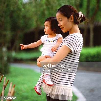 Pretty young mom holding toddler talking to her