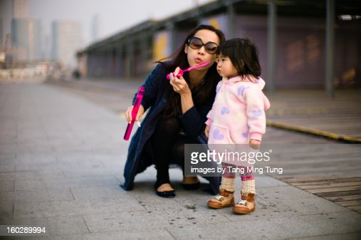 Pretty young mom playing bubble stick with baby : Stock Photo