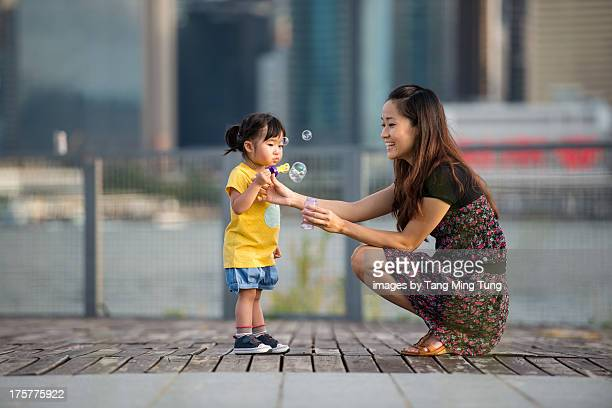 Pretty young mom playing bubble stick with toddler