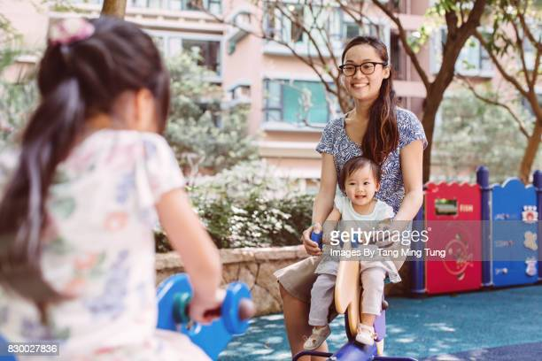Pretty young mom playing on a seesaw with her little daughter and lovely baby joyfully in a playground.