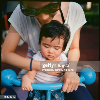 Pretty young mom playing with baby in playground : Stock Photo
