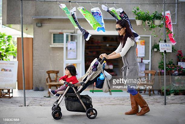Pretty young mom pushing baby stroller on street