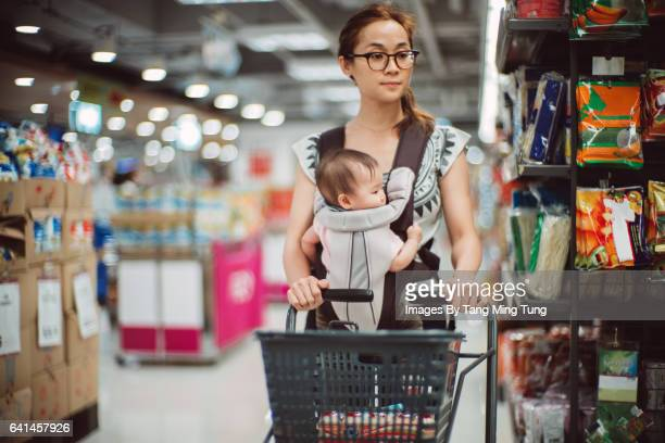 Pretty young mom shopping with baby in a supermarket