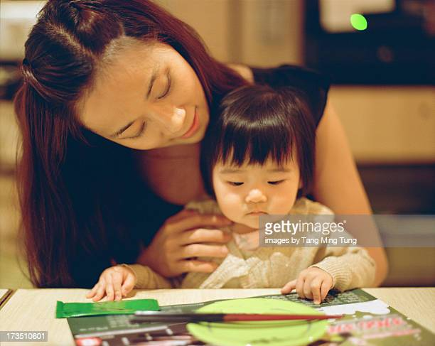 Pretty young mom talking to baby on dining table