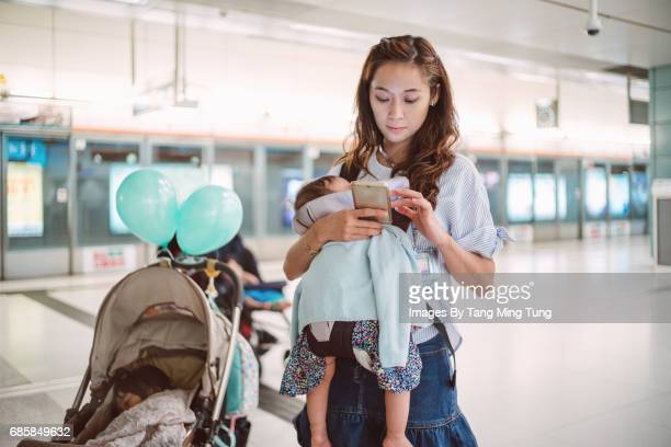 Pretty young mom using smartphone in the train platform while carrying her little baby in the baby carrier and with her elder daughter sleeping in the stroller.