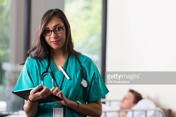Jolie jeune infirmière à l'aide de tableau numérique dans la salle patients de l'hôpital