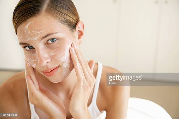 Pretty Young Woman Applying Face Cream