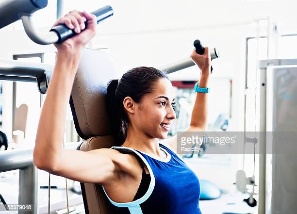 Pretty young woman does strengthening exercises in gym smiling