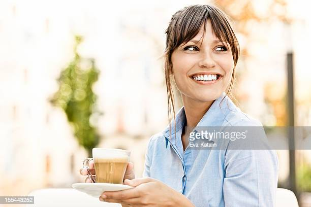 Pretty young woman drinking a cup of coffee