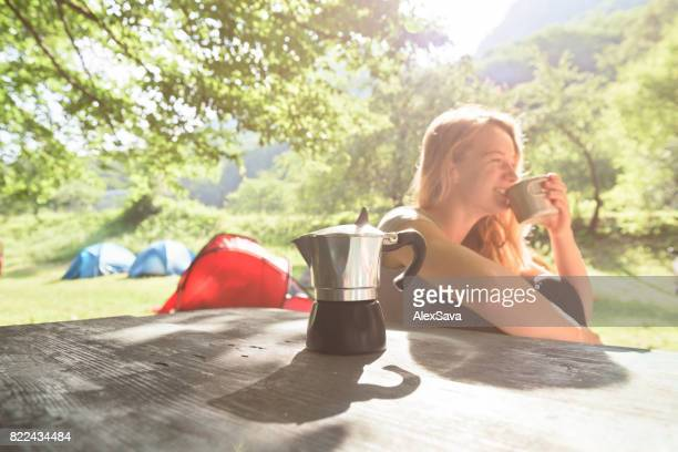 Pretty young woman enjoying her cup of coffee in camping