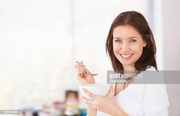 Jolie jeune femme ayant un bol de céréales