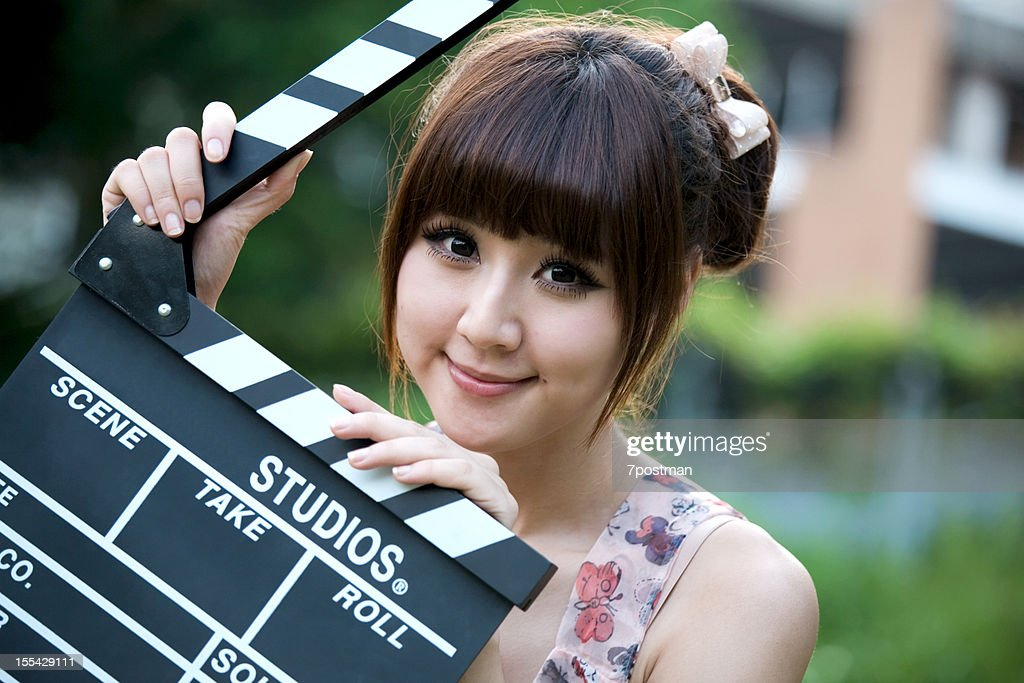 Pretty young woman holding a clapper : Stock Photo