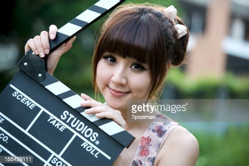 Pretty young woman holding a clapper : Bildbanksbilder