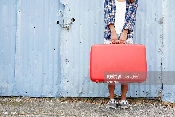 Pretty young woman holding a vintage red suitcase
