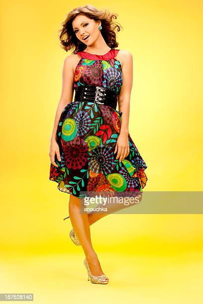 Pretty Young Woman in Summer dress portrait on yellow background