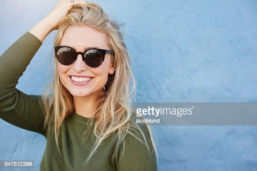 Pretty young woman in sunglasses smiling : Photo
