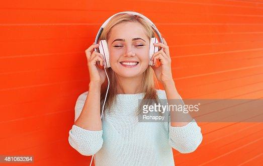 Hübsche junge Frau Hört zu und genießen Sie die Musik im Kopfhörer : Stock-Foto