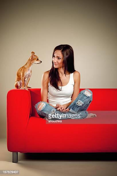 Hübsche Junge Frau auf Sofa Gespräch mit ihrem schönen chihuahua