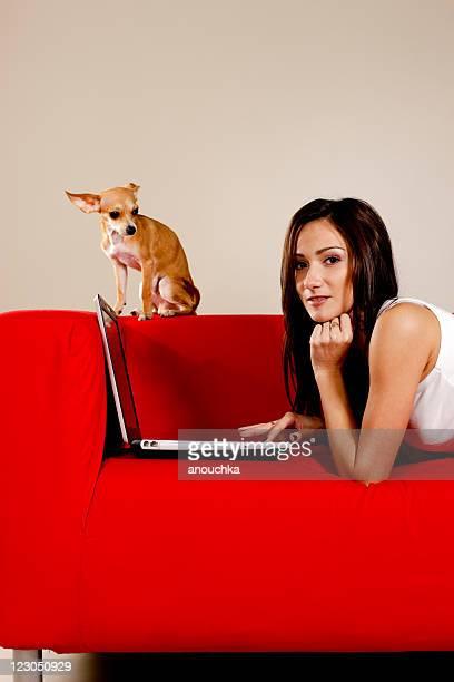 Hübsche, Junge Frau auf Sofa mit ihr chihuahua und laptop