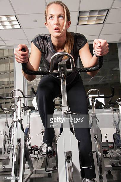 pretty young woman on exercise bike front