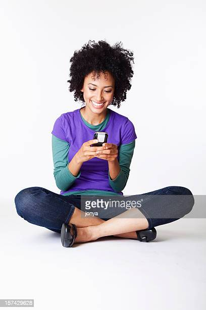 pretty young woman sitting cross-legged texting smiling