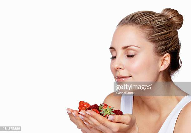 Pretty young woman smelling fresh strawberries