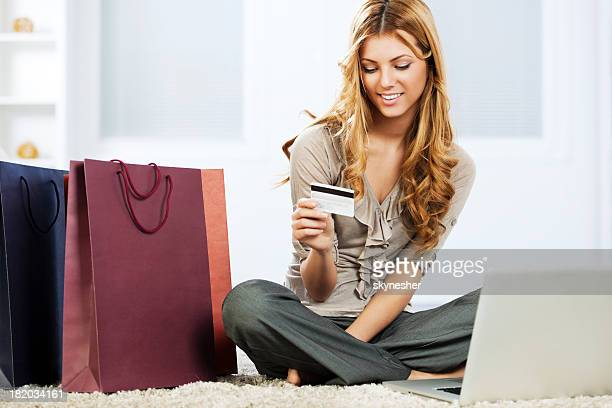 Pretty young woman smiles while shopping online