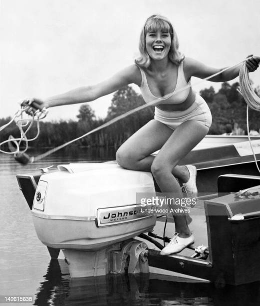 A pretty young woman tosses a tow rope from the stern of a power boat with a Johnson motor 1966