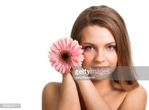 Pretty young woman with a pink flower : Stock Photo