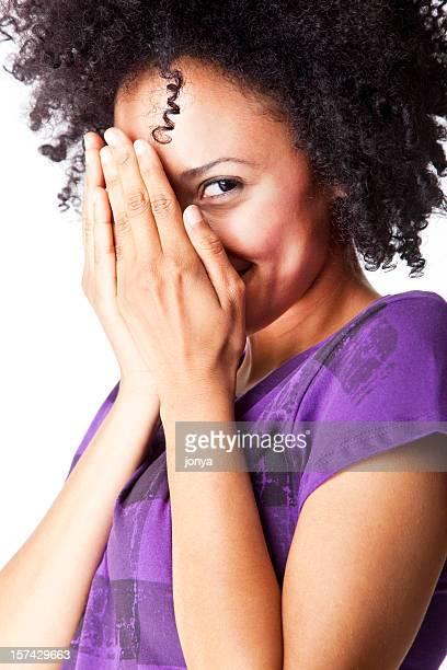 Jolie jeune femme avec des cheveux bouclés, se cacher le visage sous mains