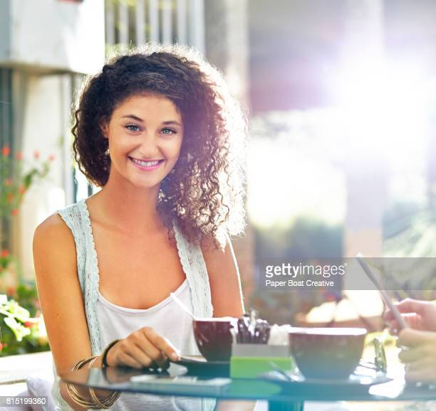 pretty young woman with curly hair smiling sitting at a cafe table with coffee on a sunny day