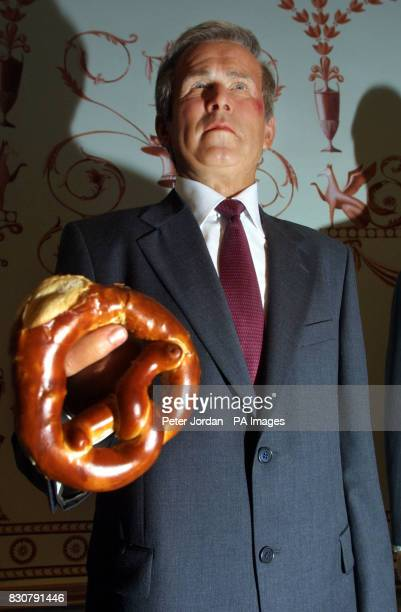 A pretzel is placed in the hand of a wax model of President George W Bush at Madame Tussaud's in London Yesterday President Bush fainted and hit his...