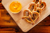 pretzels and dipping cheese on wood cutting board overhead